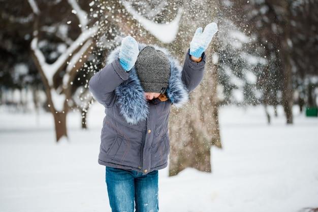 Gelukkige jongen die in sneeuw, de winterspelen spelen Premium Foto