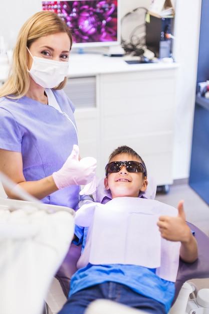 Gelukkige jongen en tandarts gesturing duimen omhoog in kliniek Premium Foto