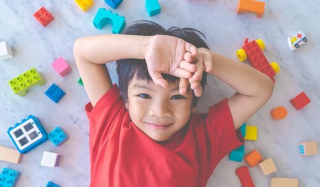 Gelukkige jongen omringd door kleurrijke stuk speelgoed blokken Premium Foto