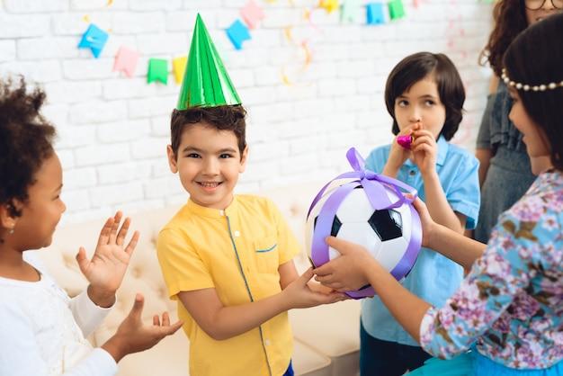 Gelukkige jongen ontvangt voetbal als verjaardagscadeau. Premium Foto