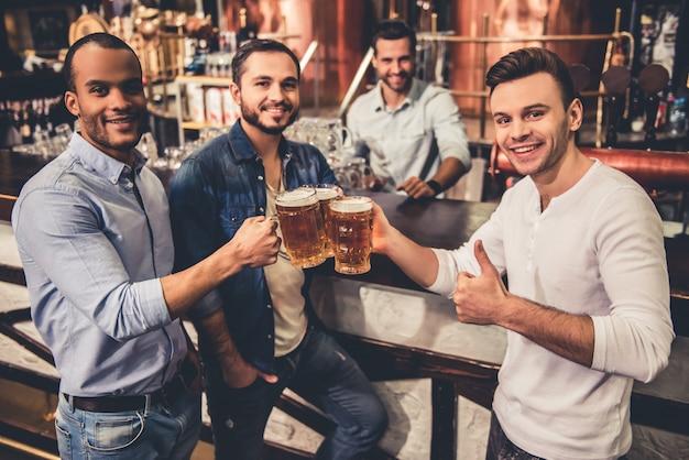 Gelukkige jongens drinken bier en kijken naar de camera. Premium Foto
