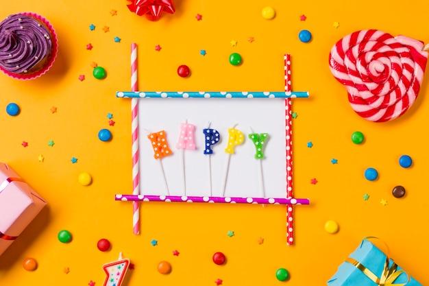 Gelukkige kaars met muffins; edelstenen; hagelslag; geschenkdozen en hartvorm lollipop op een oranje achtergrond Gratis Foto