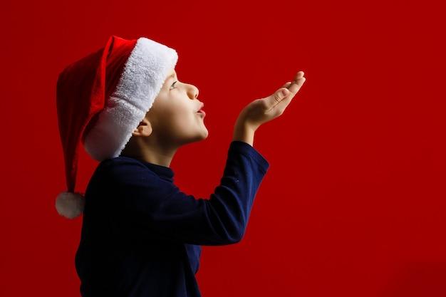 Gelukkige kerstmis van de kindholding stelt op een rode achtergrond voor Premium Foto