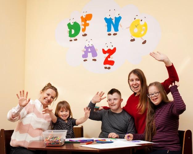 Gelukkige kinderen met het syndroom van down zwaaien en poseren Premium Foto
