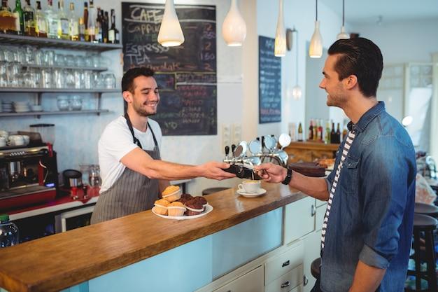 Gelukkige klant die door creditcard bij koffiewinkel betaalt Premium Foto