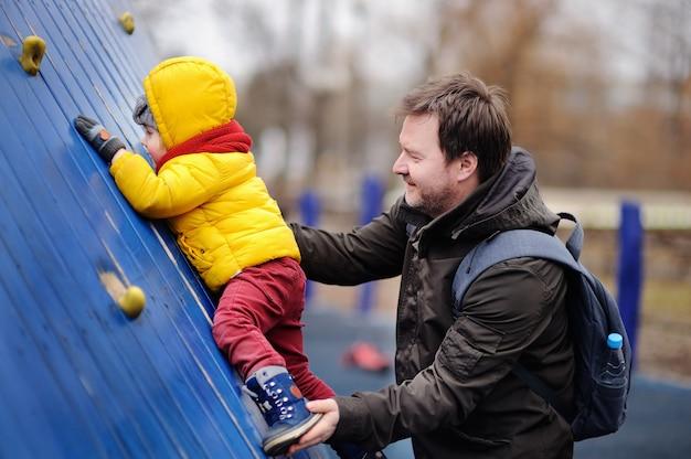 Gelukkige kleine jongen met zijn vader plezier op buitenspeeltuin. lente en herfst actieve vrijetijdsbesteding voor kinderen. Premium Foto