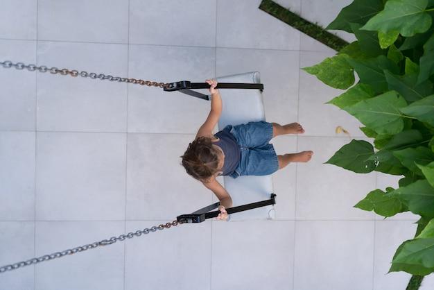 Schommel In Huis : Gelukkige kleine jongen op schommel voor zijn huis foto