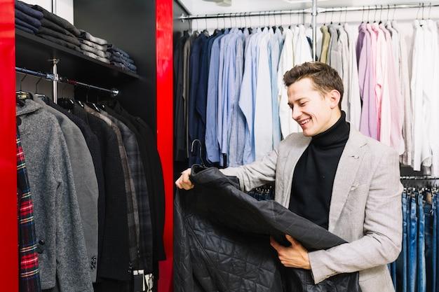 Gelukkige knappe mens die jasje in de klerenwinkel bekijkt Gratis Foto