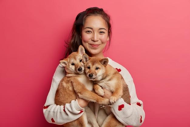 Gelukkige koreaanse vrouwelijke hondeneigenaar toont haar familieleden, staat met twee schattige stamboompuppy's, kocht jachthonden op shiba inu, brengt tijd thuis door. Gratis Foto