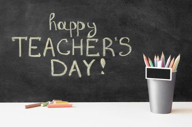 Gelukkige lerarendag op bord en potloden Gratis Foto