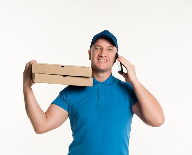Gelukkige leveringsmens dragende pizzadozen en het houden van telefoon Gratis Foto