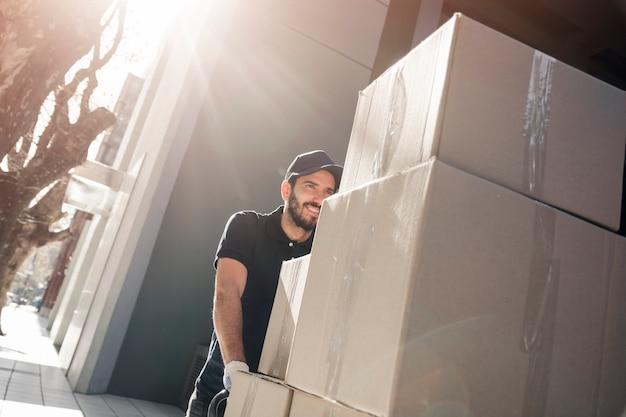 Gelukkige leveringsmens met pakketten op stoep Gratis Foto