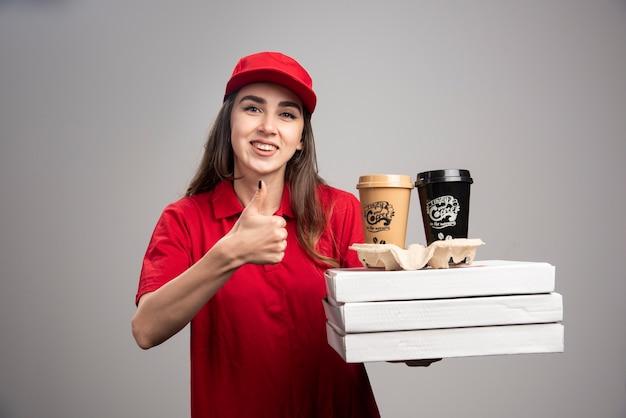 Gelukkige leveringsvrouw die duimen met pizza en koffiekopjes op grijze muur maken. Gratis Foto