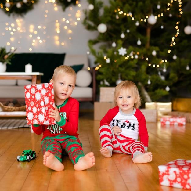 Gelukkige lieve kinderen in pyjama's spelen met kerstcadeautjes Premium Foto