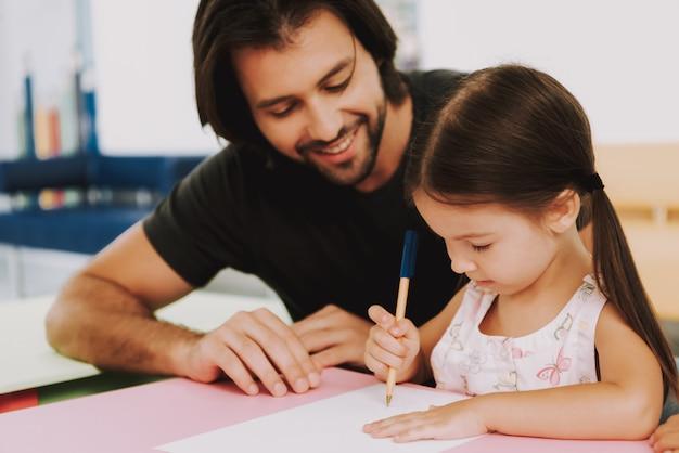 Gelukkige man en dochter tekenen in pediatrische kliniek Premium Foto