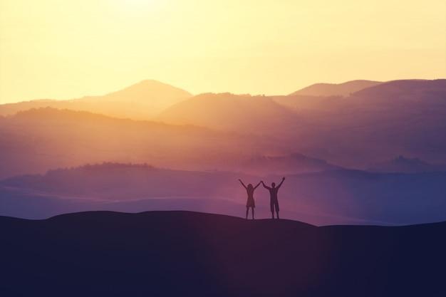 Gelukkige man en vrouw die zich op een heuvel bevinden Premium Foto
