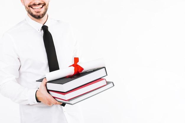 Gelukkige man met boeken en diploma Gratis Foto