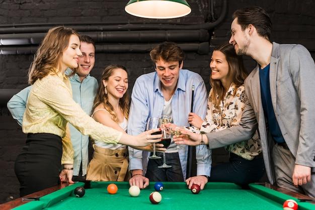 Gelukkige mannelijke en vrouwelijke vrienden die wijn in club over snookerlijst roosteren in club Gratis Foto