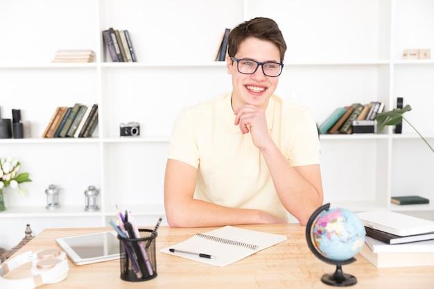 Gelukkige mannelijke studentenzitting met leeg notitieboekje Gratis Foto