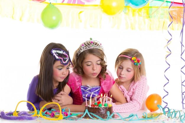 Gelukkige meisjes blazen verjaardagsfeestje taart Premium Foto