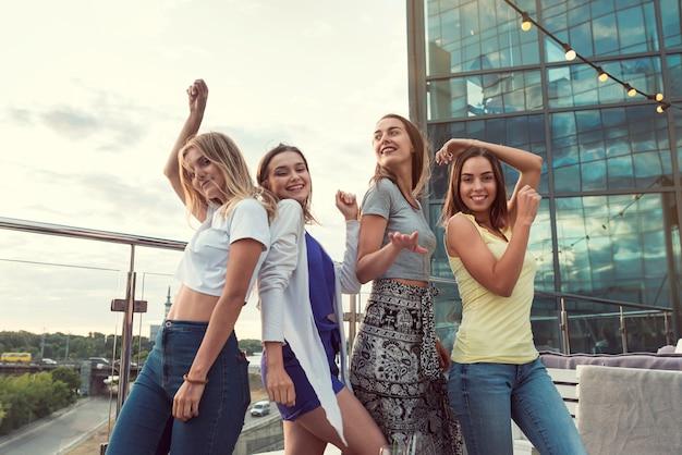 Gelukkige meisjes dansen op een terrasfeestje Gratis Foto