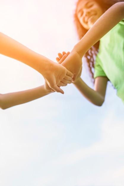 Gelukkige meisjes die hun handen stapelen die tegen hemel spelen Gratis Foto