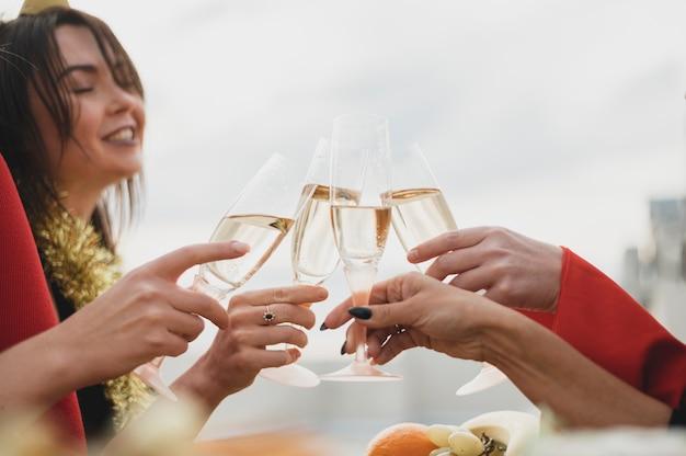 Gelukkige meisjes die omhoog glazen champagne toejuichen Gratis Foto