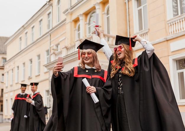 Gelukkige meisjes nemen selfie met diploma Gratis Foto