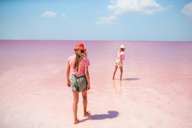 Gelukkige meisjes op een roze zoutmeer op een zonnige zomerdag. Premium Foto