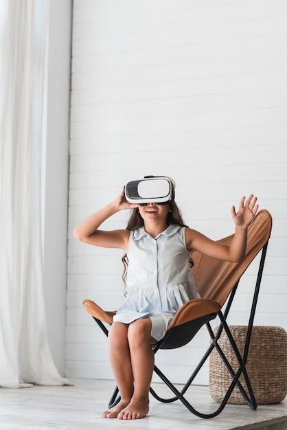 Gelukkige meisjeszitting op stoel die virtuele werkelijkheidsglazen thuis dragen Gratis Foto