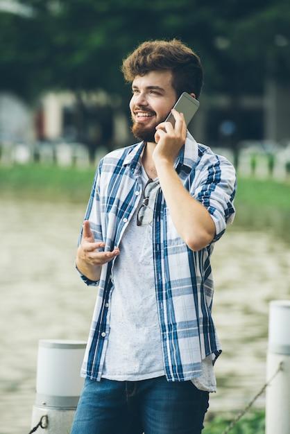 Gelukkige mens die aan zijn meisje op de telefoon spreekt die zich in openlucht bevindt Gratis Foto