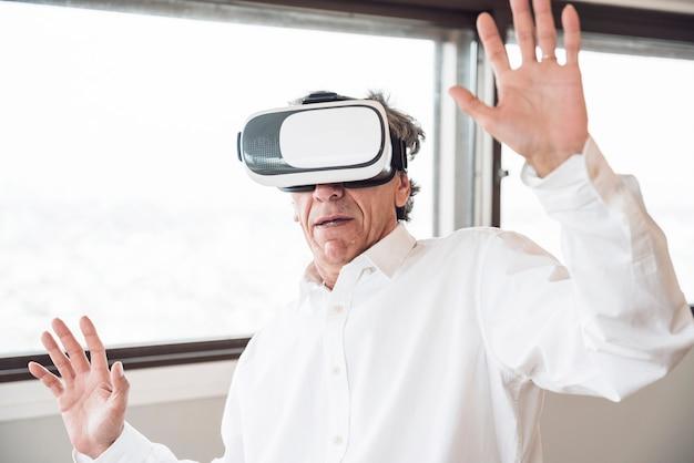 Gelukkige mens die de simulatie van de virtuele werkelijkheidshoofdtelefoon onderzoeken Gratis Foto