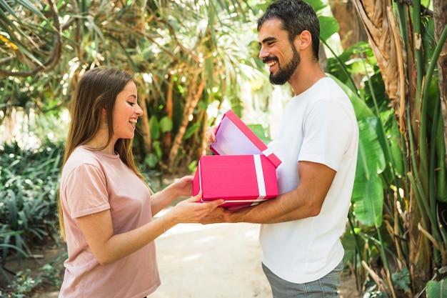 Gelukkige mens die gift tonen aan zijn meisje in park Gratis Foto