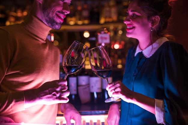Gelukkige mens die glazen wijn met vrolijke vrouw klettert Gratis Foto