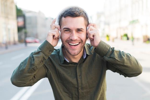 Gelukkige mens die hoofdtelefoon het luisteren muziek dragen en camera bekijken Gratis Foto