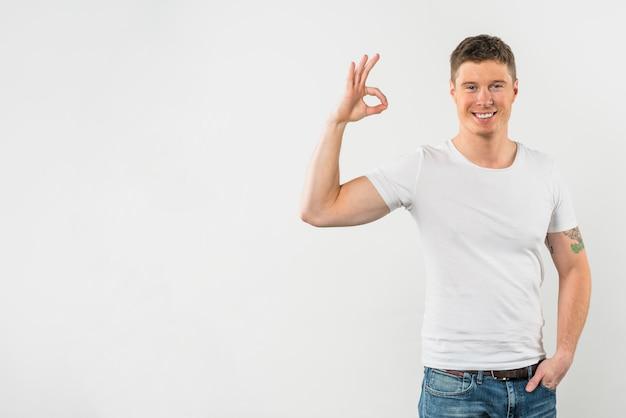 Gelukkige mens die ok teken toont tegen witte achtergrond Gratis Foto