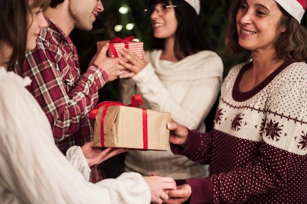 Gelukkige mensen die giften ruilen bij kerstmisviering Gratis Foto