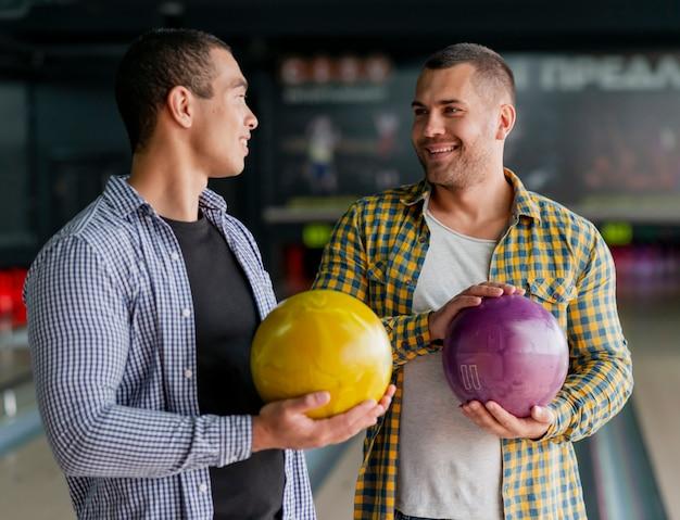 Gelukkige mensen die kleurrijke kegelenballen houden Gratis Foto