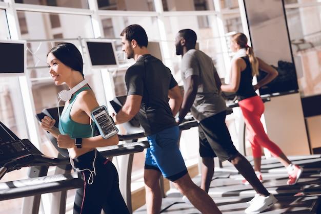 Gelukkige mensen lopen op een loopband in de sportschool. Premium Foto