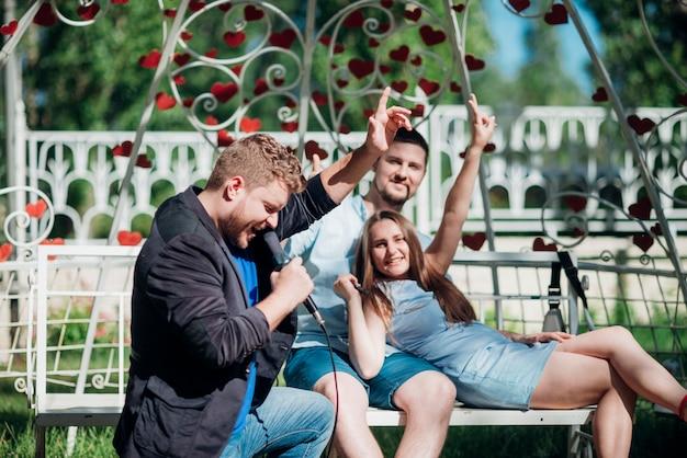 Gelukkige mensen ontspannen op bank zingen lied en gebaren overwinning Gratis Foto