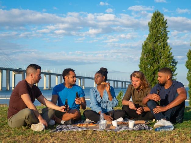Gelukkige mensen praten en bier drinken tijdens zomerpicknick. goede vrienden praten en bier drinken. concept van picknick Gratis Foto