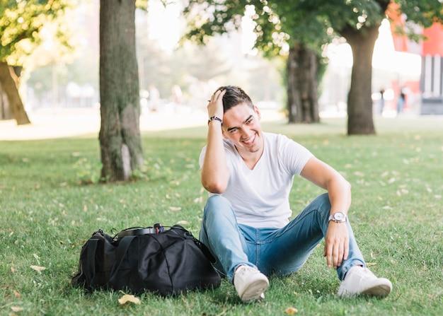 Gelukkige mensenzitting op gras in park Gratis Foto