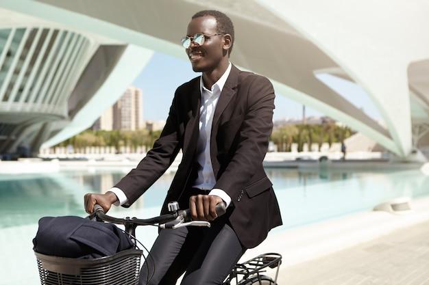 Gelukkige milieubewuste afro-amerikaanse werknemer in zwart formeel pak en zonnebril die de fiets kiest boven het openbaar vervoer of de auto om naar kantoor te gaan, genietend van een rit in een stedelijke omgeving Gratis Foto