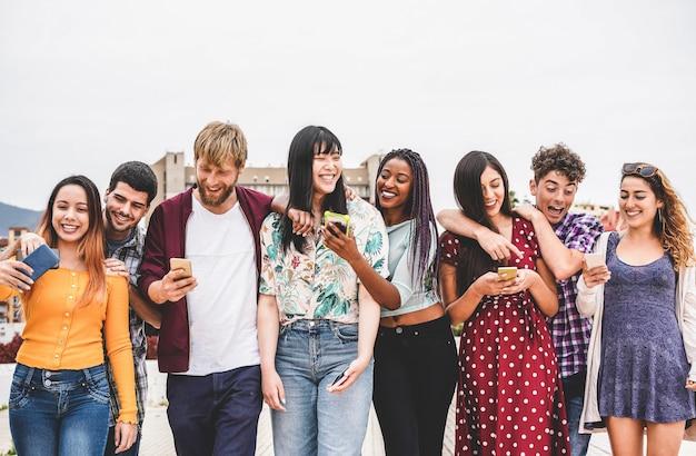 Gelukkige millennialsvrienden die samen buiten universiteit lopen Premium Foto