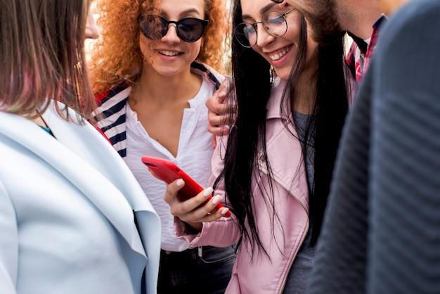 Gelukkige modieuze groep vrienden die het mobiele telefoonscherm bekijken Gratis Foto