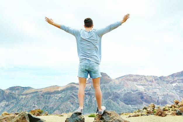 Gelukkige modieuze mens in toevallige hipsterkleren die zich op de klip van berg met opgeheven handen aan de zon bevinden en succes vieren Gratis Foto