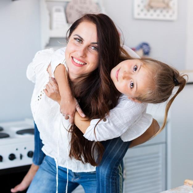 Gelukkige moeder die haar aanbiddelijk meisje houdt Gratis Foto
