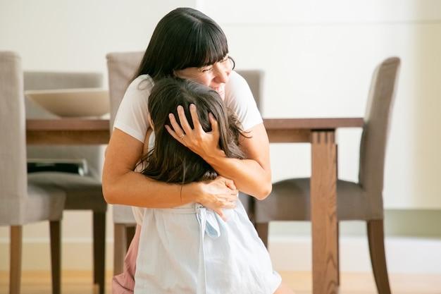Gelukkige moeder die haar mooie dochter met beide handen omhelst. Gratis Foto