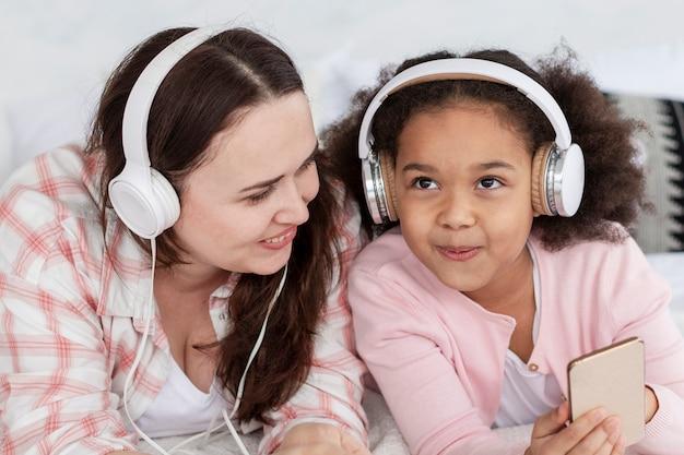 Gelukkige moeder en dochter die aan muziek luisteren Gratis Foto