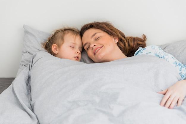 Gelukkige moeder en dochter die samen in huis slapen Gratis Foto